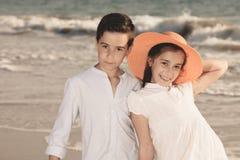 Jongen en meisje op het strand, zij met een oranje hoed stock foto