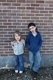 Jongen en meisje tegen muur royalty-vrije stock afbeeldingen