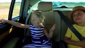 Jongen en meisjes het berijden in de auto stock footage