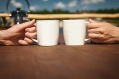 Jongen en meisjes het rusten en het drinken thee dichtbij meer op terras royalty-vrije stock afbeeldingen
