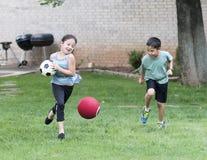 Jongen en meisjes het spelen in het gras stock afbeelding