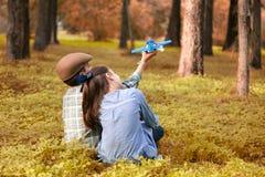 Jongen en meisjes het spelen met een stuk speelgoed vliegtuig in een bos stock foto's