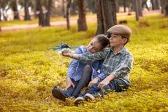 Jongen en meisjes het spelen met een stuk speelgoed vliegtuig in een bos royalty-vrije stock foto's