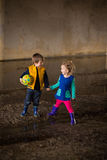 Jongen en meisjes het spelen in modder Stock Foto