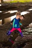 Jongen en meisjes het spelen in modder Stock Foto's