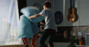 Jongen en meisjes speelhoofdkussenstrijd op bed stock videobeelden