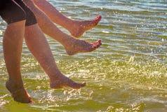 Jongen en meisjes sprekende voeten in het water op een zonnige dag Royalty-vrije Stock Fotografie