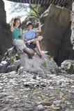 Jongen en meisjes (10-12) zitting op rots die stenen werpen Royalty-vrije Stock Afbeelding