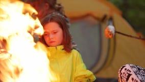 Jongen en meisjesbraadstukheemst over een kampvuur stock footage