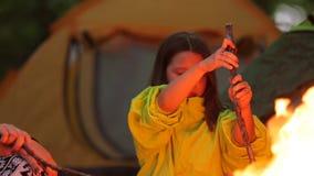 Jongen en meisjesbraadstukheemst over een kampvuur stock video