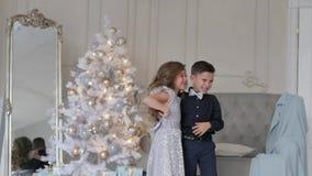 Jongen en meisjesclose-up op een achtergrond van de Kerstmisboom kinderen in mooie uitrustingen stock video