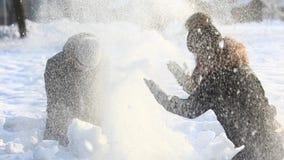 Jongen en meisjesspel met sneeuw in park Bloem in de sneeuw Sneeuw overal Witte kleur stock videobeelden