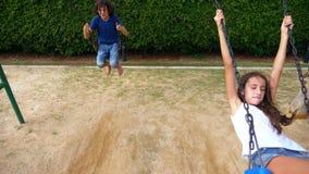 Jongen en meisjestiener die op een schommeling met naakte voeten op het groene gazon van de binnenplaats van zijn huis slingeren stock video
