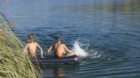 Jongen en meisjesvlotters op opblaasbare matras stock footage