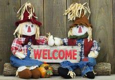 Jongen en meisjesvogelverschrikkers die op logboek zitten die rood houten welkom teken houden Royalty-vrije Stock Foto