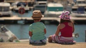 Jongen en meisjeszitting op een pijler stock video
