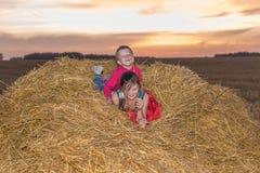 Jongen en meisjeszitting op een stapel van stro Stock Afbeelding