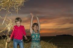 Jongen en meisjeszitting op een stapel van stro Stock Foto