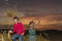 Jongen en meisjeszitting op een stapel van stro Royalty-vrije Stock Afbeelding