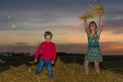 Jongen en meisjeszitting op een stapel van stro Stock Fotografie