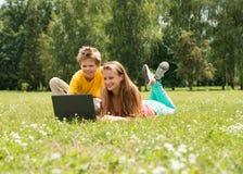 Jongen en meisjeszitting op gras met laptop, online in park Twee glimlachende tienersstudenten met laptop die op weide rusten Ond Stock Afbeelding