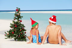Jongen en Meisjeszitting op Strand met Kerstboom en Hoed Stock Afbeeldingen