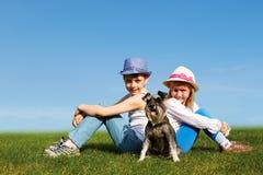 Jongen en meisjeszitting rijtjes op het gras op een de zomerdag Royalty-vrije Stock Afbeelding