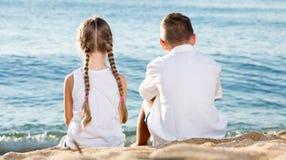 Jongen en meisjeszittingsrug royalty-vrije stock afbeelding