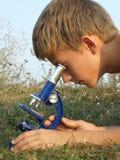 Jongen en microscoop Stock Afbeelding