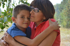 Jongen en moeder die in bos koesteren Royalty-vrije Stock Afbeelding