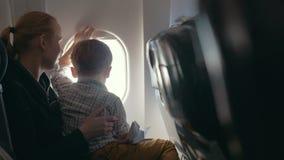 Jongen en moeder die buiten door vliegtuig kijken stock video
