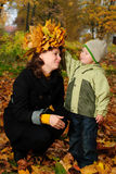 Jongen en moeder in herfstpark stock foto's