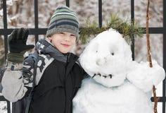 Jongen en sneeuwman Stock Foto