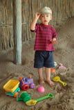 Jongen en speelgoed op strand Stock Foto's