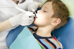 Jongen en tandarts tijdens een tandprocedure Stock Fotografie