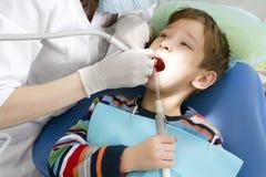 Jongen en tandarts tijdens een tandprocedure Stock Foto's