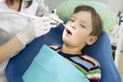 Jongen en tandarts tijdens een tandprocedure Stock Afbeelding