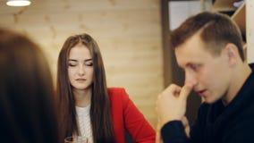 Jongen en twee meisjes het lachen en bespreking in koffie stock video