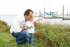 Jongen en vader bij jachthaven Stock Foto's