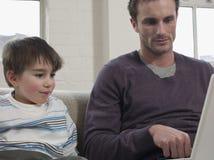 Jongen en Vader Looking At Laptop binnenshuis stock fotografie