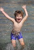 Jongen en waterdalingen Gelukkig kind op zee De zomer Overzeese vakantie Vakantie Het jonge geitje speelt in het water Pret grapp stock foto