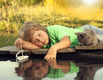 Jongen en zijn het geliefde katje spelen met een boot van pijler in vijver Stock Fotografie