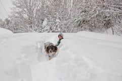 Jongen en zijn hond uit in een sneeuwonweer royalty-vrije stock fotografie