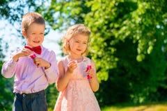 Jongen en zijn meisje met zeepbels Stock Foto
