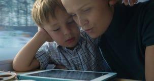 Jongen en Zijn Moeder die op Cartooins in Tablet letten