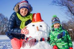 Jongen en zijn moeder met een sneeuwman royalty-vrije stock foto's