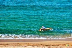 Jongen en zijn moeder op strand met opblaasbare vlotter royalty-vrije stock foto