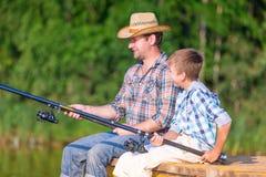 Jongen en zijn vader die togethe vissen Stock Foto's