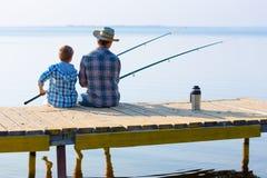 Jongen en zijn vader die togethe vissen Stock Foto