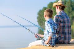 Jongen en zijn vader die togethe vissen Stock Afbeelding